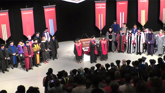 faculty in regalia on stage
