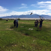 grass field with film crew, mountains in background