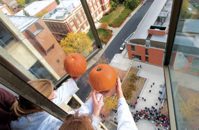 two people holding pumpkins out a 12th-story window