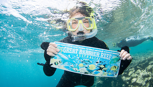 "student underwater with snorkle mask and ""Great Barrier Reef"" sign"
