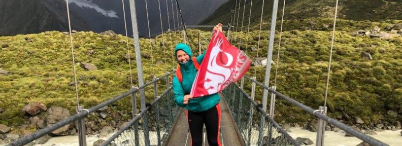 student on bridge with WSU flag