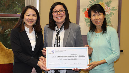 Yoko Yanagimoto presents a grant check to Carmen Lugo-Lugo and Kayo Niimi