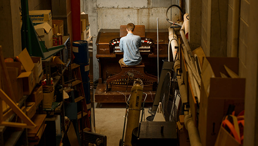 Thomas LeClair in the basement of Webster Hall working on the pipe organ.