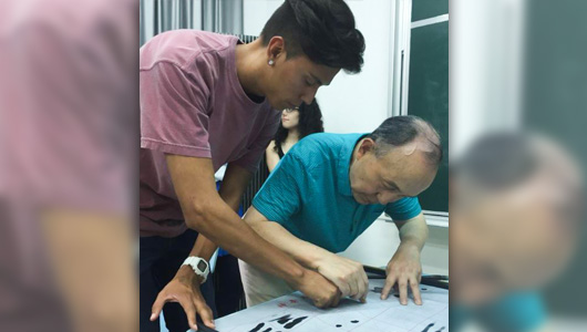Student and instructor printing Chinese characters with ink.