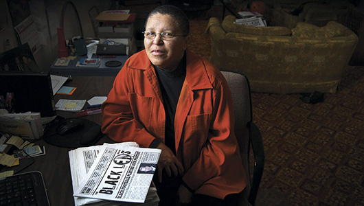 Sandra Williams and a stack of Black Lens newspapers.