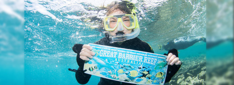 woman snorkling underwater, holding sign