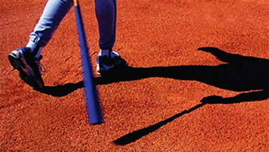A baseball player holding a bat casts a shadow across the orange gravel of the playfield.