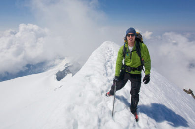 Scott pictured at the top of a snowy mountain peak, wearing cold weather hiking gear.
