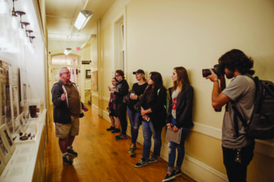 Students in a hallway attending a guided tour by Richard Burrows.