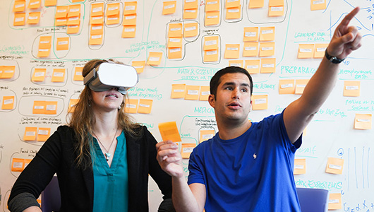 Two people sitting in front of a wall covered in sticky notes. One person wearing a VR headset sits next to another person pointing off screen.