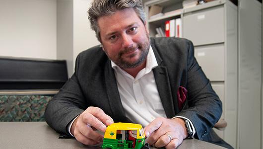 Dean Luethi holding a small toy rickshaw.