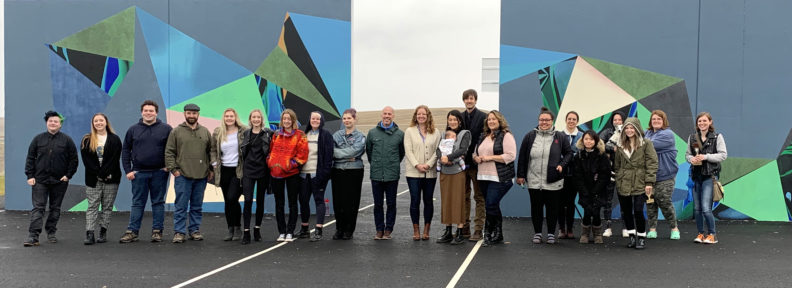 group of people in front of two outdoor murals