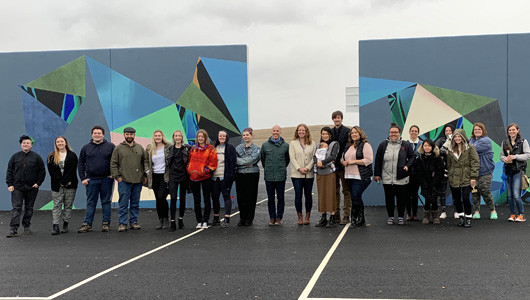About 20 WSU students along with faculty project leaders and Kamiak Elementary principal Evan Hecker stand in front of 2 murals depicting the molecular vision of thermochromatic pigment.
