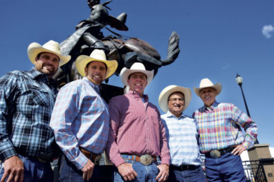 Five cowboys pose with statue of bronco rider and horse