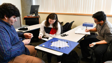 Three students playing a board game.
