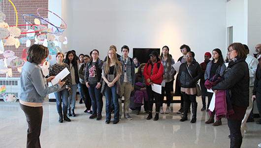 A group of students listening to a presentation by faculty.