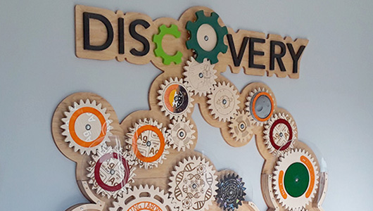 "Wall art made with wooden cogs. Title reads, ""Discovery""."