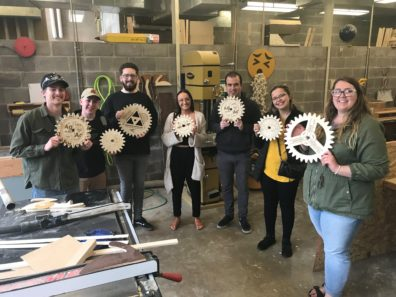 Students and instructor hold up their cogs.