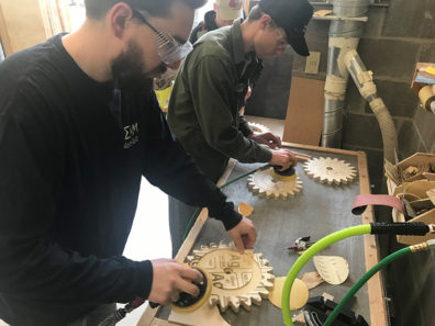 Students working on wooden cogs.