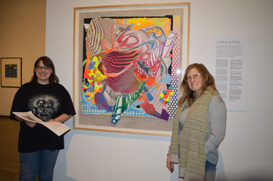 Nora Loney and Linda Russo stand beside the brightly colored abstract painting Loney chose to write her poem about.