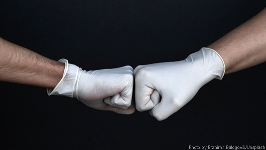 Gloved fistbump, photo by Branimir Balogović/Unsplash