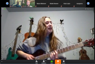 Zoom meeting screen shot of Brooke Rowland singing while playing guitar in a room with 2 guitars and a ukulele on the wall behind her.