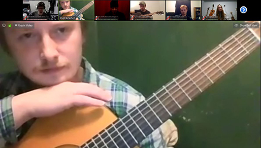 Zoom meeting screenshot of Joel Roeber with his guitar with faces of other Songwriters Roundtable participants in small frames.