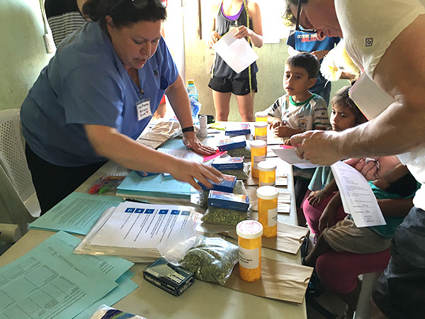 Anna Maria Rodriguez-Vivaldi talks to children and parents at a table filled with medicine bottles and literature.