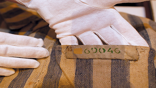 close up gloved hands and the number detail of a Holocaust prisoner uniform.