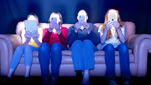 Four people sit on a couch with their faces lit up but obstructed by the digital devices they're holding in front of them., photograph, Samantha Wiltermood.