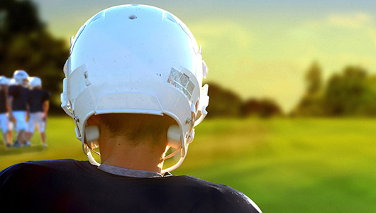 Youth wearing a football helmet looks out across a field.