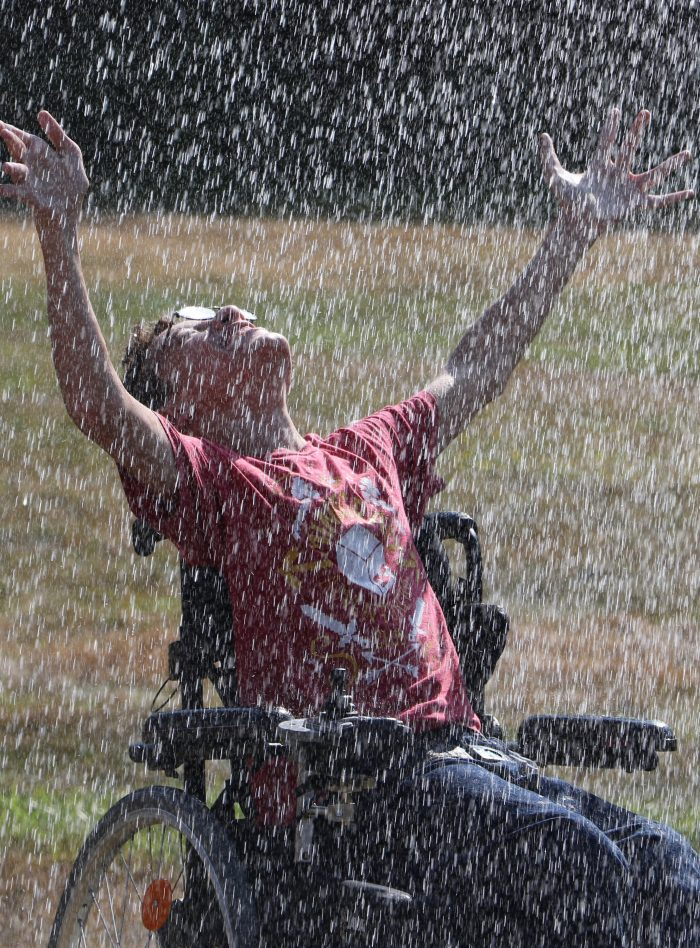 Person in a wheelchair with arms raised high enjoying themselves while water falls from above during a summer activity.