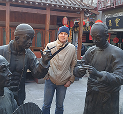 Sergey Lapin stands with life-size statues of 3 men in a market-areapark in Tianjin, China.