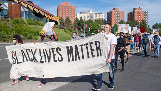Students march holding a Black Lives Matter banner on the WSU Pullman campus.