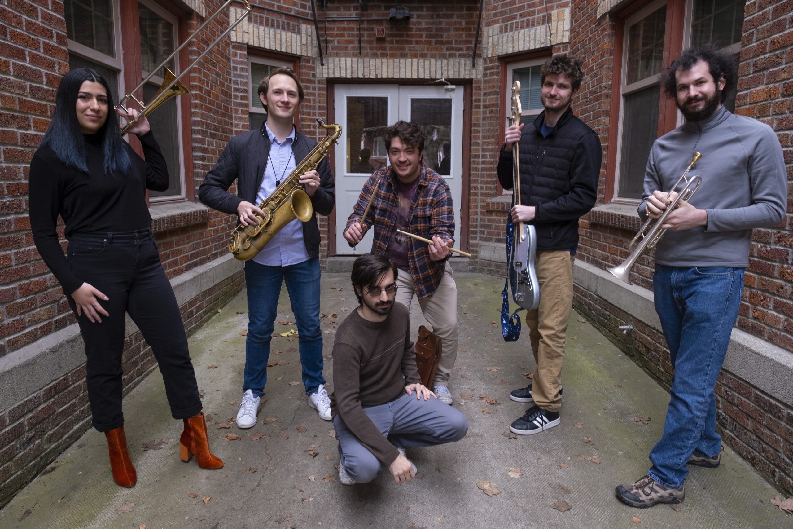 Musicians pose in an alley.