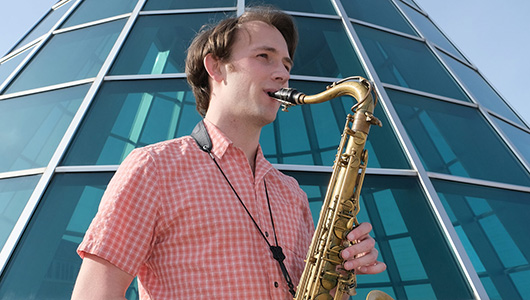 Brandt Fisher playing a saxophone.