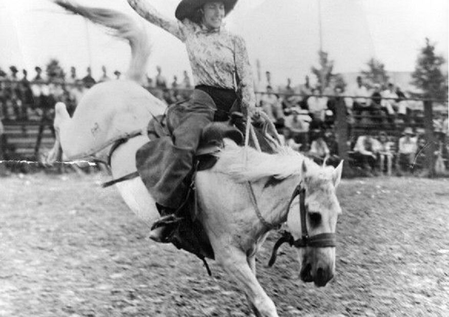 A woman riding a horse in a rodeo.