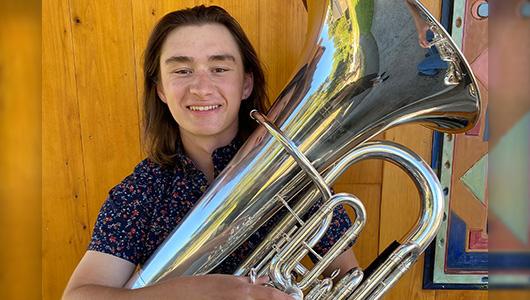 Timothy Schrader holding a tuba.