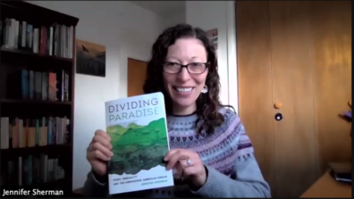 Jennifer Sherman holding her new book, Dividing Paradise: Rural Inequality and the Diminishing American Dream.