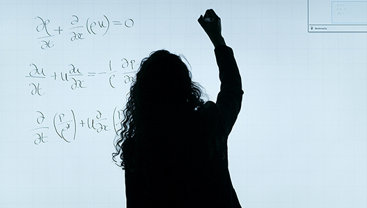 Silhouette of a person writing on a white board.