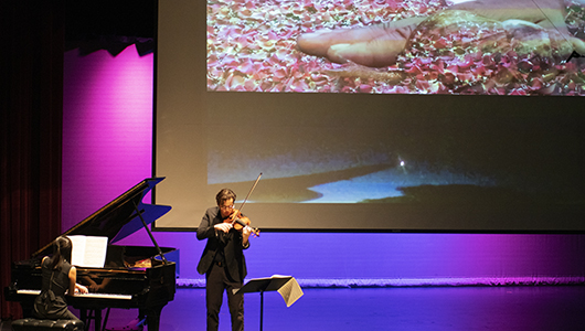 Pianist and violinist perform on stage in front of video projection.
