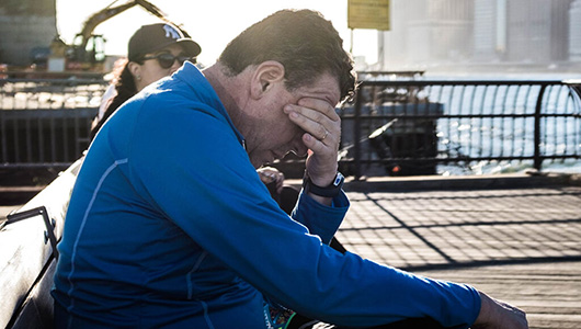 A man sits on a public bench rubbing his eyes.