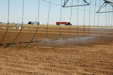 Sprinklers on a center pivot arm spraying a plowed, bare field, with trucks in the background