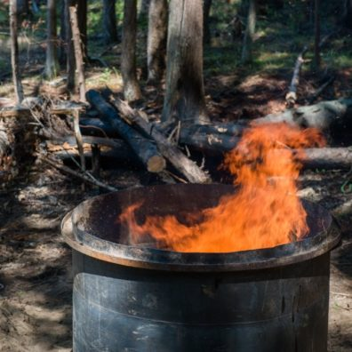 barrel with flames coming out, in a forest setting