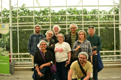 Nine people in a greenhouse, clustered in front of a trellis system, with tall vegetable plants in the background.