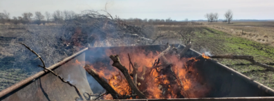 Oil tank kiln with burning branches inside, and a pile of branches in the surrounding ag field