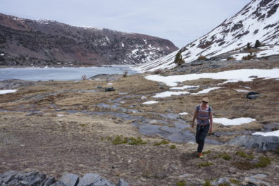 Hiker in a high elevation area, with a small lake and ridges with patchy snow in the background
