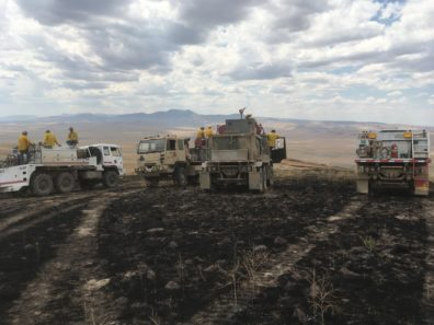 Multiple trucks with firefighters on a severely burned area