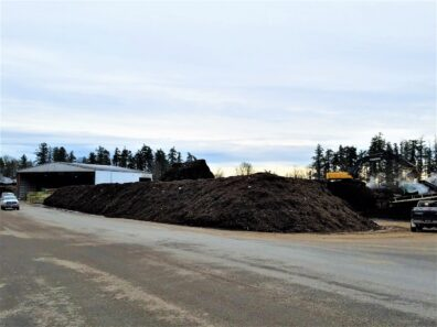 Large compost pile, with facility in the background