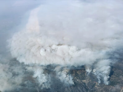 Mountainous landscape with smoke billowing up from wildfires